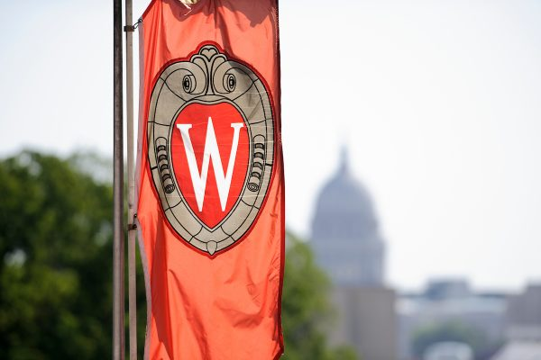 "A ""W"" crest banner hanging on Bascom Hill at the University of Wisconsin-Madison is pictured in relation to an out-of-focus view of the Wisconsin State Capitol dome"