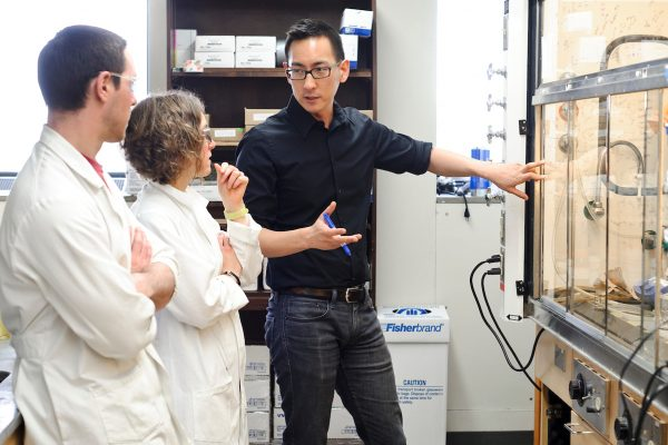 Tehshik Yoon (right), associate professor of chemistry, holds a discussion with graduate research assistant Travis Blum (left) and research associate Dani Schultz in a lab at UW-Madison